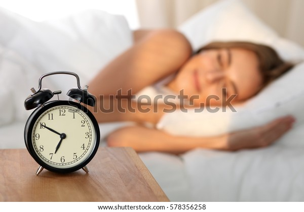 Beautiful young woman sleeping and smiling while lying in bed comfortably and blissfully on the background of alarm clock is going to ring. Sunbeam on her face.