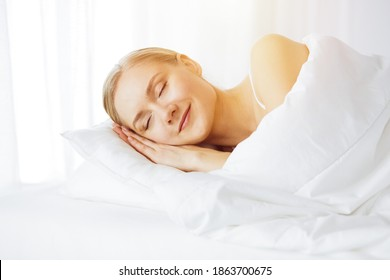 Beautiful young woman sleeping in sunny bedroom comfortably and blissfully. Waking up in fairy morning
