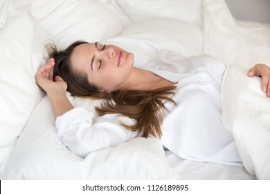 Beautiful young woman sleeping well in cozy comfortable bed on soft orthopedic pillow and cotton linen, attractive lady resting lying asleep on white sheets enjoying healthy good deep sleep or nap