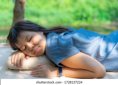 Beautiful young woman sleeping while lying down on outdoor garden  and blissfully. Sunbeam dawn on her face with background of green tree nature. Concept of rest and relaxation.