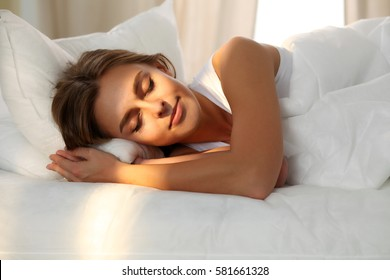 Beautiful young woman sleeping while lying in bed comfortably and blissfully. Sunbeam dawn  on her face