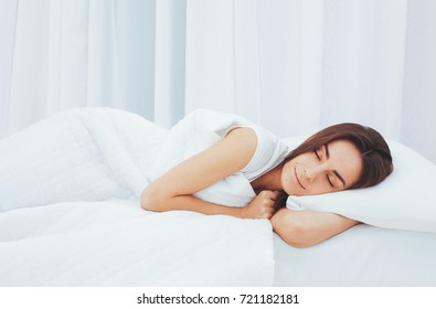 Beautiful young woman sleeping in a white bed in a large spacious bedroom