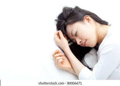 beautiful young woman sleeping in white bed