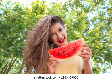 Beautiful young woman with slice of tasty watermelon outdoors