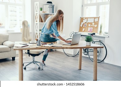 Beautiful young woman in smart casual wear using laptop while working in the office