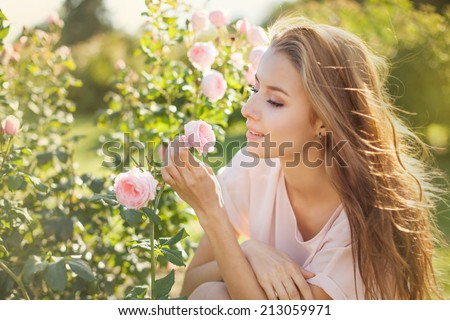 Beautiful young woman smelling a rose flower