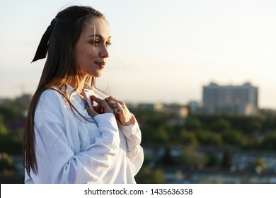 Beautiful young woman smiles tender standing on the rooftop in the rays of evening sun