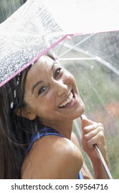 Beautiful young woman smiles towards the camera while holding an umbrella under a spray of water. Vertical shot.