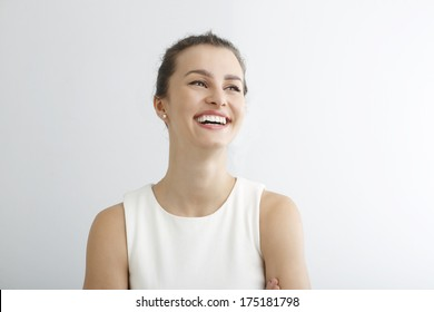 Beautiful young woman smiling against white background.