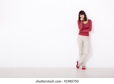 Beautiful young woman smiling, against a white wall with copyspace on the left side.