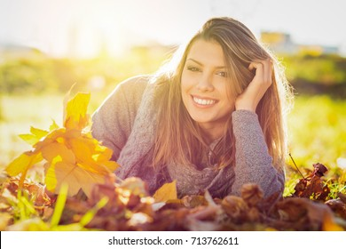 Beautiful young woman smiling in autumn in park. Closeup portrait of gorgeous happy girl in leaves on sunny fall day. Vibrant colors, retouched.