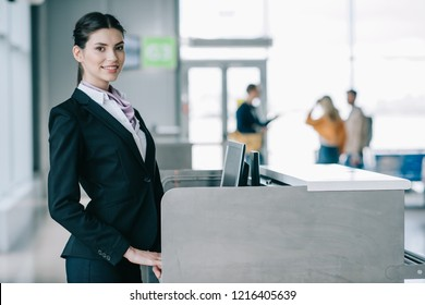 beautiful young woman smiling at camera while working at check-in desk in airport