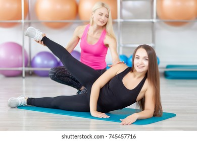 Beautiful young woman smiling to the camera working out with her fitness instructor doing leg raise exercise positivity beauty vitality wellness wellbeing health happiness training concept.