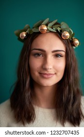 beautiful young woman smiling in christmas holiday flower crown with baubles