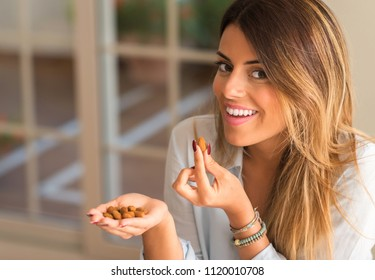 Beautiful young woman smiling and eating nuts at home. Healthy concept.