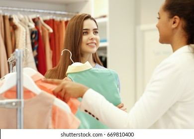 Beautiful young woman smiling getting help from a shop assistant while choosing clothes at the store shopping shopaholic buying buyer customer service client people communication advice sale concept