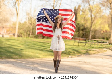 beautiful young woman smiling and happy with flag of America celebrating on independence day 4th of july in central park of New York