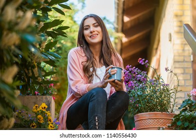 Beautiful young woman smiling and looking at camera, sitting on home terrace, holding a mug drinking a hot beverage. Hobby and resting leisure concept.