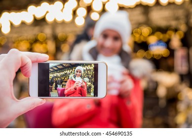 A beautiful young woman smiling in to a phone for a picture on the christmas market. - Shutterstock ID 454690135