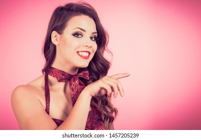 Beautiful young woman smiling and pointing.  Ideal for advertising your message
