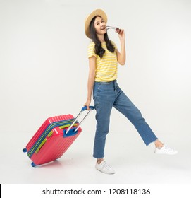 Beautiful young woman smiling and pulling pink color luggage isolated on white background.Woman going to summer vacation.Travel trip funny.