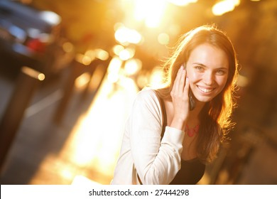 Beautiful young woman smiling and talking on cell phone on sunny street. ShallowDOF.