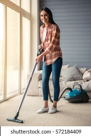 Beautiful young woman is smiling and using a vacuum cleaner while cleaning floor at home