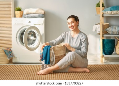 Beautiful young woman is smiling while doing laundry at home.