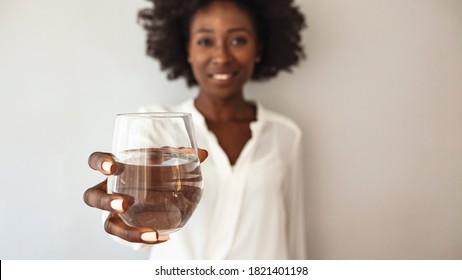 Beautiful young woman smiling while holding a glass of water at home. Lifestyle concept. Happy young woman showing drinking glass with water at home. Hydration is her beauty secret