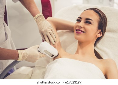 Beautiful young woman is smiling while doctor in medical gloves is undertaking the laser epilation of her armpits