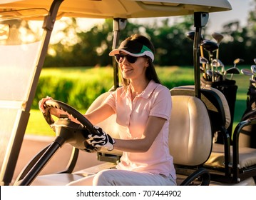 Beautiful young woman is smiling while driving a golf cart