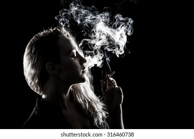 Beautiful young woman smoking a cigarette over black background