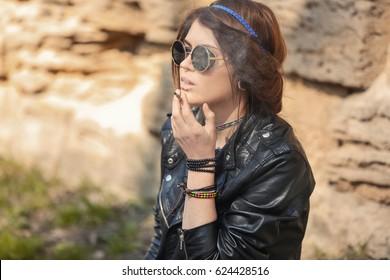 Beautiful young woman smoking weed outdoors