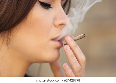 Beautiful young woman smoking weed outdoors, closeup