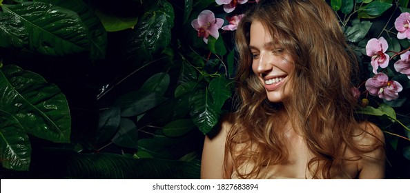 Beautiful young woman with smooth tanned skin laughs cheerfully while standing against the background of exotic plants and flowers. Natural cosmetics, skin care.
