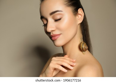 Beautiful young woman with snail on her neck against beige background