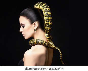 beautiful young woman with Snake on her head like a hair. Brunette girll with fashion make up and jewelry earrings. Beauty close up studio shot
