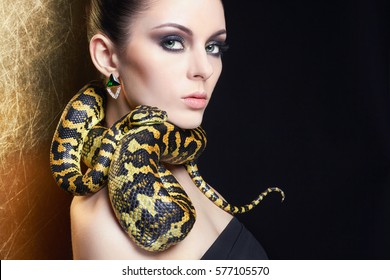 beautiful young woman with Snake.Brunette girl with fashion perfect make up. Beauty close up studio shot.jewelry earrings