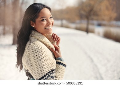Beautiful young woman in the snow in winter