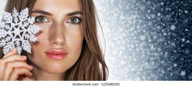 Beautiful young woman and snowflake on winter background. New year holiday concept. Space for text. Banner.