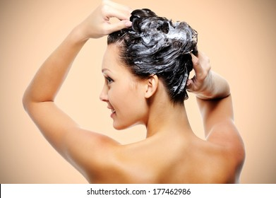 Beautiful young woman soaping her head