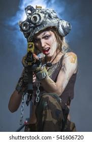 Beautiful young woman - soldier is shooting a machine gun
