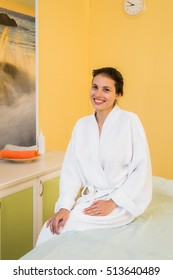 Beautiful young woman in a spa dressed in white terry cloth robe waiting for massage.