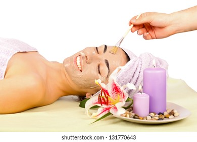 Beautiful young woman at spa with facial mask relaxing.