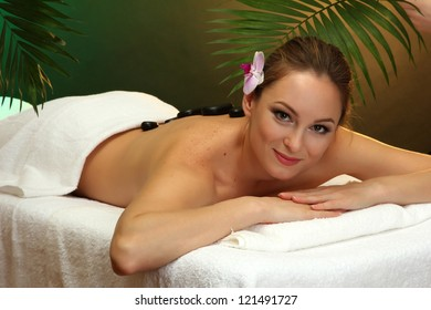 beautiful young woman in spa salon with spa stones, on green background