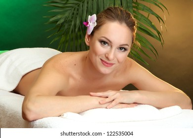 beautiful young woman in spa salon, on green background