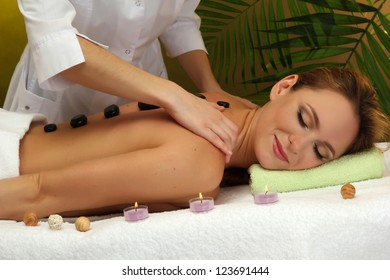 beautiful young woman in spa salon getting massage with spa stones, on green background