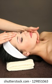 Beautiful young woman in spa salon taking head massage, on dark background