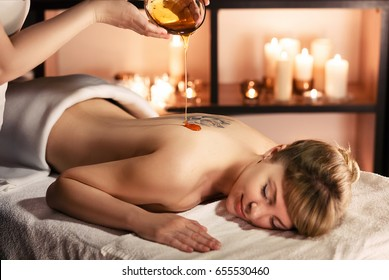 Beautiful young woman in spa salon having spa massage therapy with honey procedure. Honey massage concept on candle background