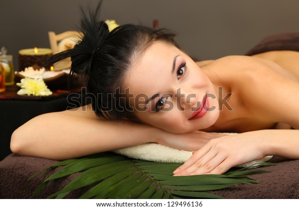 Beautiful young woman in spa salon, on dark background